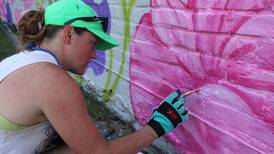 Petunia mural painter finds chill moment on scorching afternoon